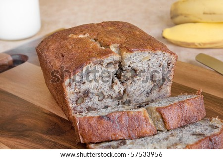 sliced loaf of walnut banana bread with bananas and milk in the background - stock photo