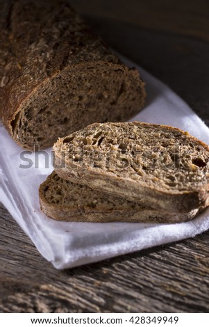 Sliced Loaf of Whole Wheat Bread on Rustic Background - stock photo
