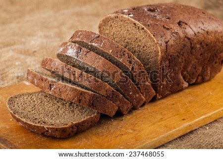 sliced loaf rye bread on a wooden board - stock photo