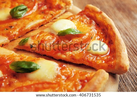 Sliced Margherita pizza on wooden background, close up