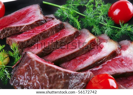sliced meat on dark plate with vegetables - stock photo