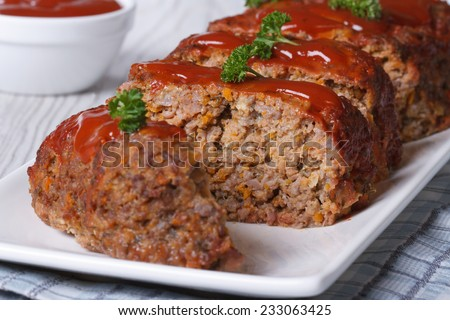sliced meatloaf with ketchup and parsley closeup on a white plate, horizontal  - stock photo