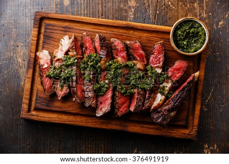 Sliced medium rare grilled beef barbecue Ribeye steak with chimichurri sauce on cutting board on dark background - stock photo