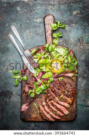 Sliced medium rare grilled beef barbecue steak served with fresh green salad and cutlery on rustic  cutting board , top view.  Meat food - stock photo