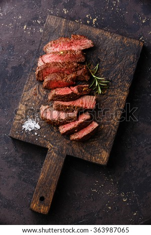 Sliced medium rare grilled Beef steak on wooden cutting board  - stock photo