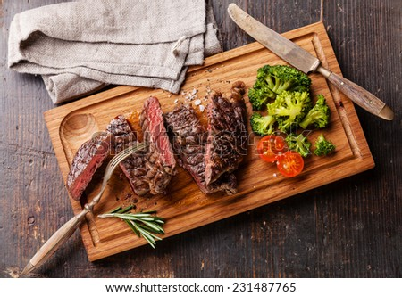 Sliced medium rare grilled Beef steak Ribeye with broccoli on cutting board on wooden background - stock photo