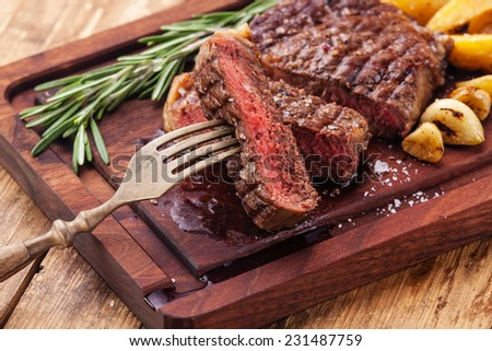 Sliced medium rare grilled Beef steak Ribeye with roasted potato wedges on cutting board on wooden background - stock photo