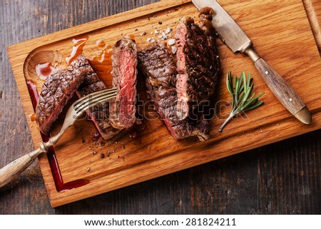 Sliced medium rare grilled Beef steak Ribeye with rosemary on cutting board on wooden background - stock photo
