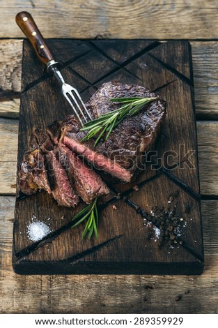 Sliced medium rare grilled beef steak with salt, pepper and rosemary on meat cutting board on dark wooden background - stock photo