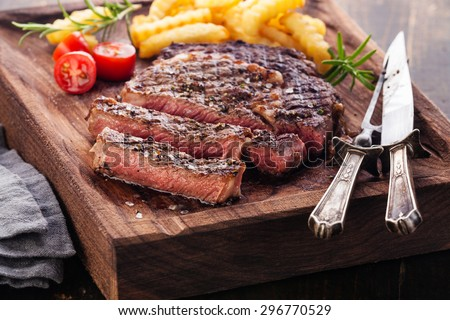 Sliced medium rare grilled Steak Ribeye with french fries on serving board block on wooden background - stock photo