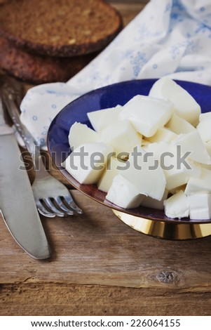 sliced mozzarella cheese in a bowl on the old wooden background. health and diet food.