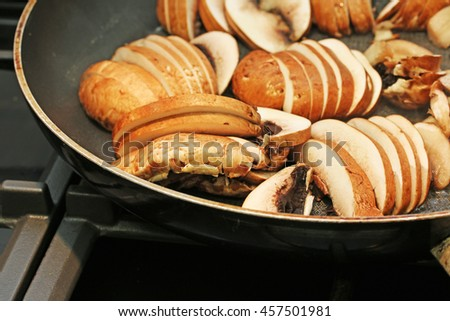 Sliced mushrooms frying in a frying pan