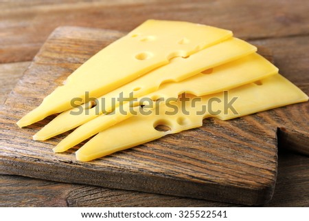 Sliced of cheese on wooden background - stock photo