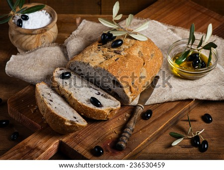 Sliced olive bread of wholemeal, black olives and olive oil on a rustic wooden background - stock photo