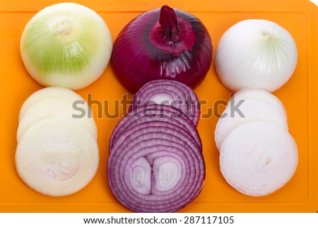 Sliced onions three varieties of the orange plastic kitchen board - stock photo