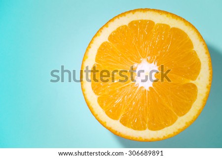 sliced orange fruit isolated on blue blackground, pop art color concept - stock photo