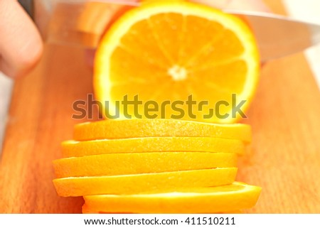 sliced orange particles to a steel knife blades on display slice of orange, the second one cutting circles on a wooden stand, holding the hand of fruit in the kitchen