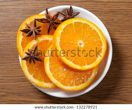 Sliced orange with anise on the saucer