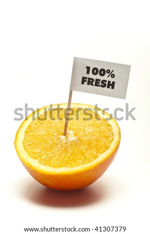 "sliced orange with flag ""100% fresh"" in front of white background"