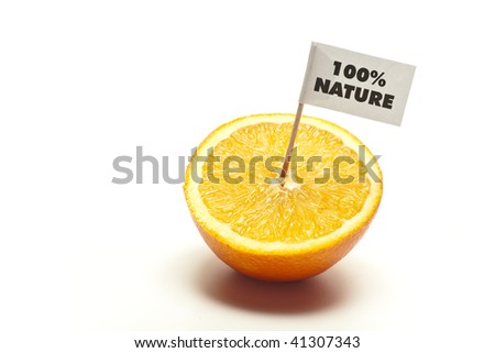 "sliced orange with flag ""100% nature"" in front of white background"