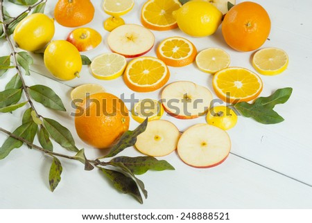 sliced oranges, apples and lemons on white wood
