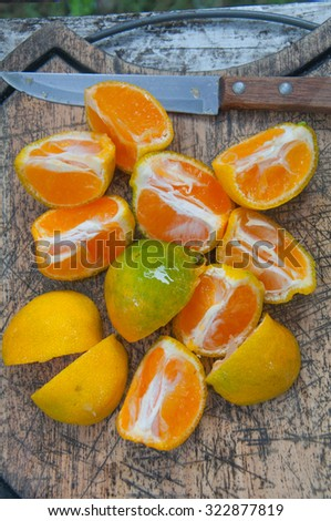 sliced oranges on a wooden cutting board - stock photo