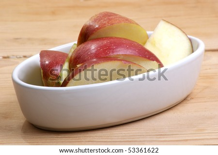 sliced organic apple in a white bowl