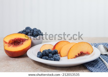 Sliced peaches and blueberries are served on a white plate - stock photo