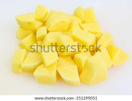 Sliced, peeled raw potatoes on a board - stock photo
