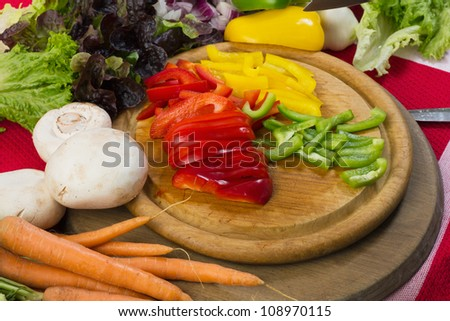 Sliced pepper and vegetables on a wooden board, vegetarian studio shot for healthy food - stock photo