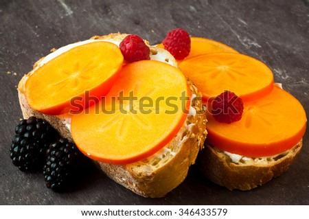 Sliced persimmon fruit with cream cheese on freshly baked corn bread. Served with fresh raspberries and blackberries on a stone slate table top.