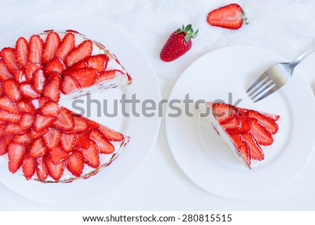 Sliced piece of gourmet homemade celebration strawberry cake sweet dessert food with whipped cream and fresh strawberries on white kitchen table background. Rustic style and natural light. Top view. - stock photo