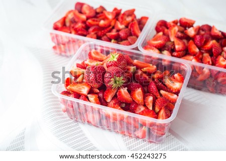 sliced pieces of strawberries in clear containers on white textile background