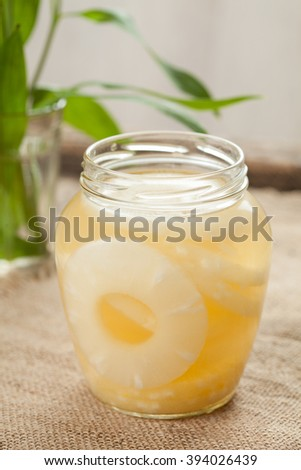 Sliced pineapple rings with juice in glass on vintage cloth background