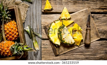 Sliced pineapple with a full box. On a wooden background. Top view - stock photo