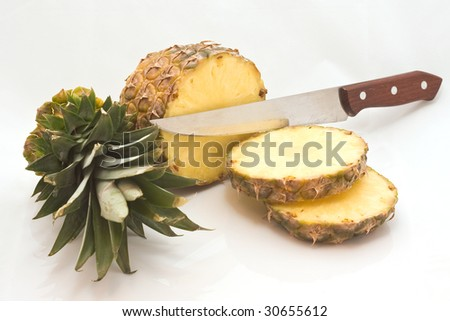 sliced pineapple with knife isolated on white - stock photo