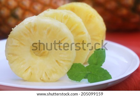 Sliced pineapple with mint leaves on a plate - stock photo
