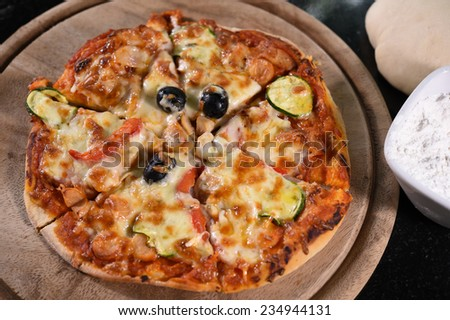 Sliced pizza close-up on wooden board. - stock photo