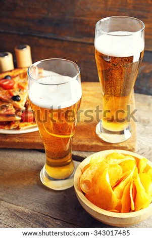 Sliced pizza served with beer on wooden table - stock photo