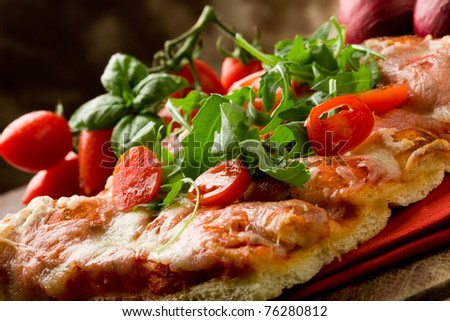 sliced pizza with arugula and cherry tomatoes on wooden table - stock photo