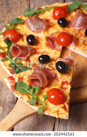 Sliced pizza with ham, tomatoes, black olives and arugula close-up vertical   - stock photo