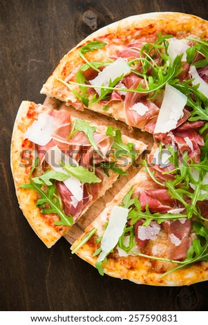 Sliced pizza with prosciutto (parma ham), arugula (salad rocket) and parmesan on dark wooden background top view. Italian cuisine. - stock photo