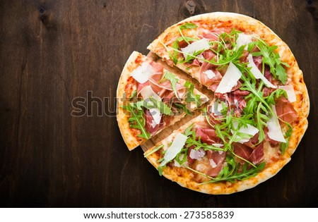 Sliced pizza with prosciutto (parma ham), arugula (salad rocket) and parmesan on dark wooden background top view. Italian cuisine. Space for text. - stock photo