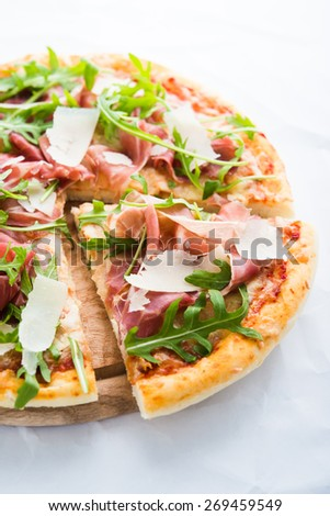 Sliced pizza with prosciutto (parma ham), arugula (salad rocket) and parmesan on white background close up. Italian cuisine. - stock photo