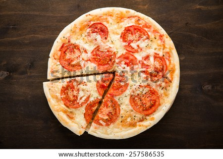 Sliced pizza with tomato, cheese and dry basil on dark wooden background top view. Italian cuisine. - stock photo