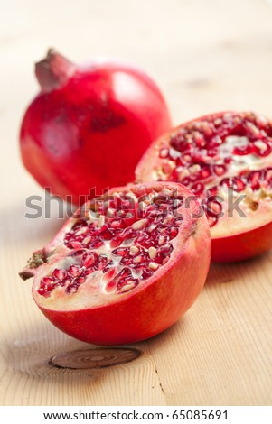 sliced pomegranate on wooden table - stock photo