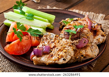 Sliced pork grilled with vegetables on ceramic brown plate - stock photo