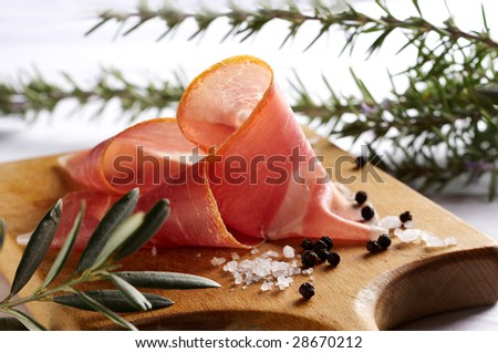 Sliced prosciutto with different herbs and seasoning on wooden desk - stock photo