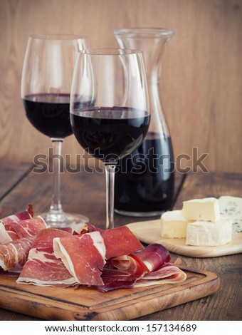 sliced prosciutto with red wine and olives  - stock photo