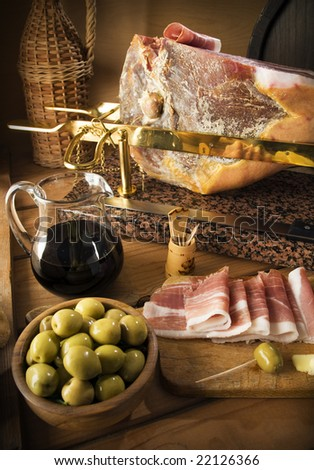 sliced prosciutto with red wine and olives close up shoot